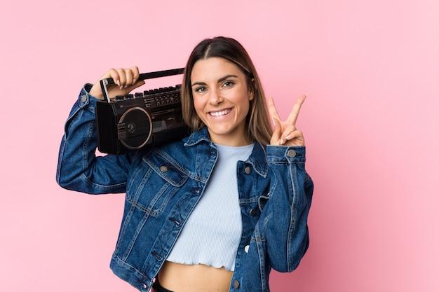 Jovem mulher segurando um radiocassete, mostrando sinal de vitória e sorrindo amplamente