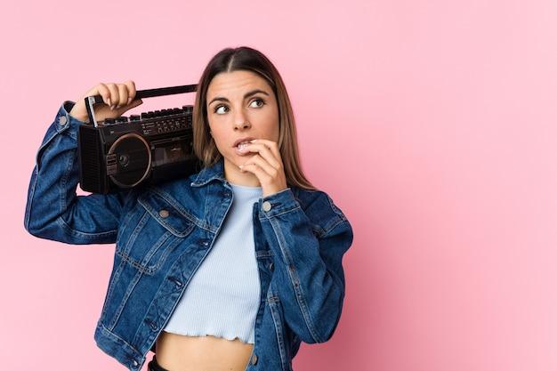 Jovem mulher segurando um radiocassete, relaxado, pensando em algo