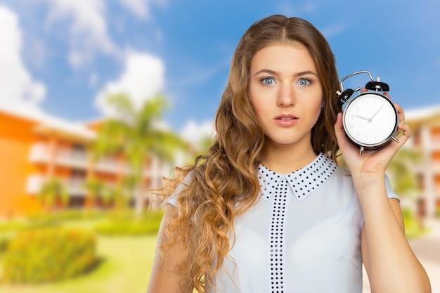 Jovem mulher segurando um relógio. conceito de gerenciamento de tempo