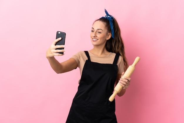 Jovem mulher segurando um rolo de massa fazendo uma selfie