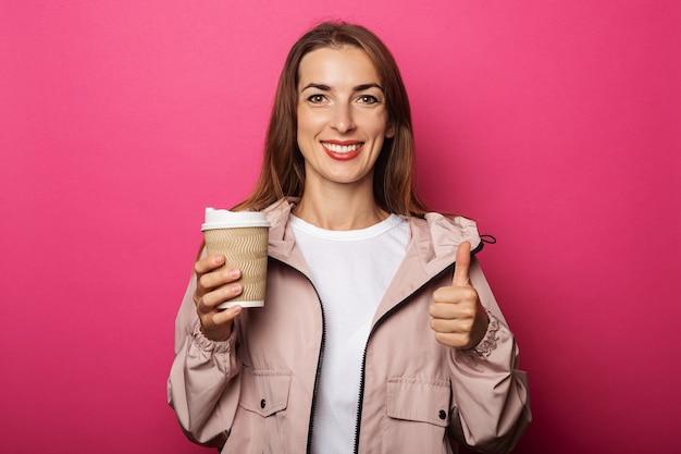 Jovem mulher segurando um rolo de papel e mostrando o polegar na superfície rosa
