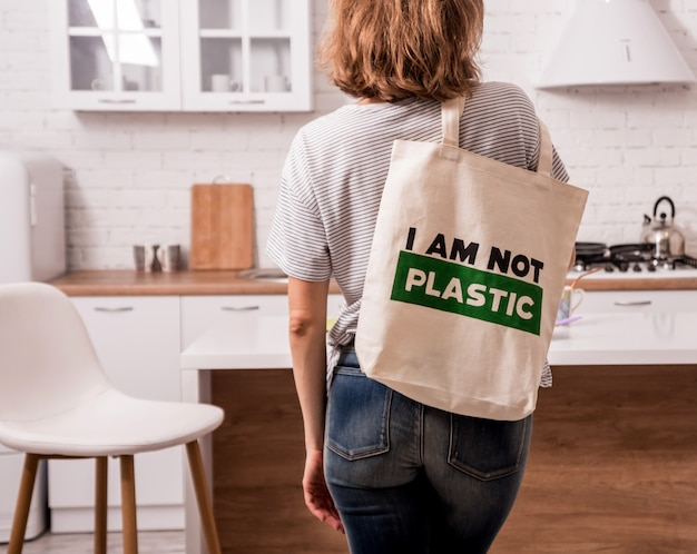 Jovem mulher segurando um saco de pano na cozinha