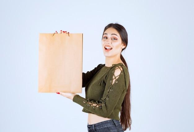Jovem mulher segurando um saco de papel com uma expressão feliz em fundo branco.