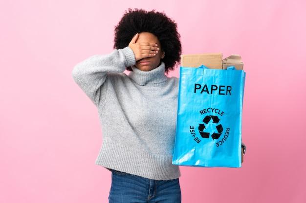Jovem mulher segurando um saco de reciclagem isolado nos olhos de cobertura colorida pelas mãos. não quero ver algo