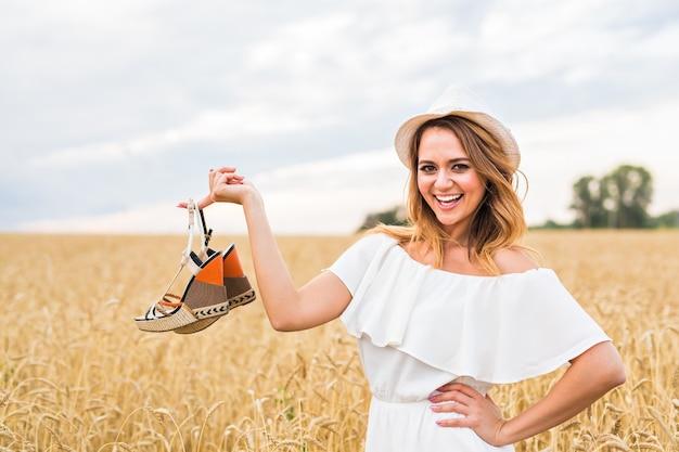 Jovem mulher segurando um sapato - conceito de venda, consumismo e pessoas
