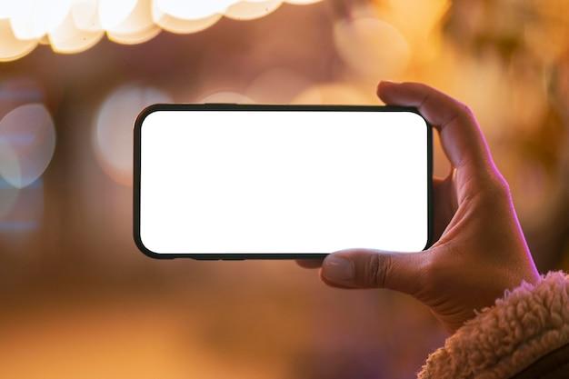 Jovem mulher segurando um smartphone em branco com efeito bokeh ao redor