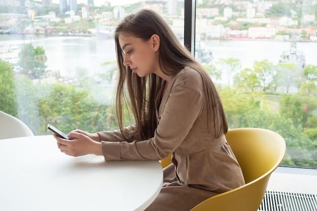 Jovem mulher segurando um telefone celular enquanto está sentada em um café perto da janela