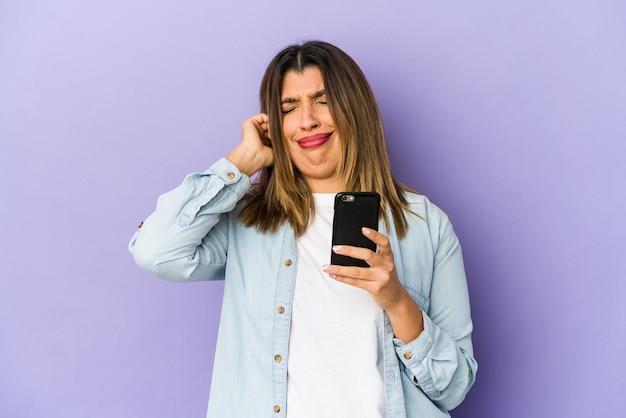 Jovem mulher segurando um telefone isolado, cobrindo as orelhas com as mãos Foto Premium