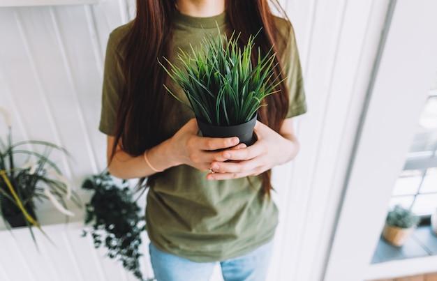 Jovem mulher segurando um vaso com uma planta decorativa
