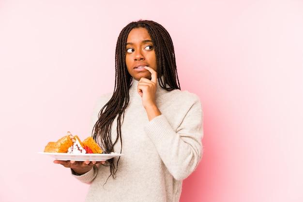 Jovem mulher segurando um waffle relaxado pensando em algo