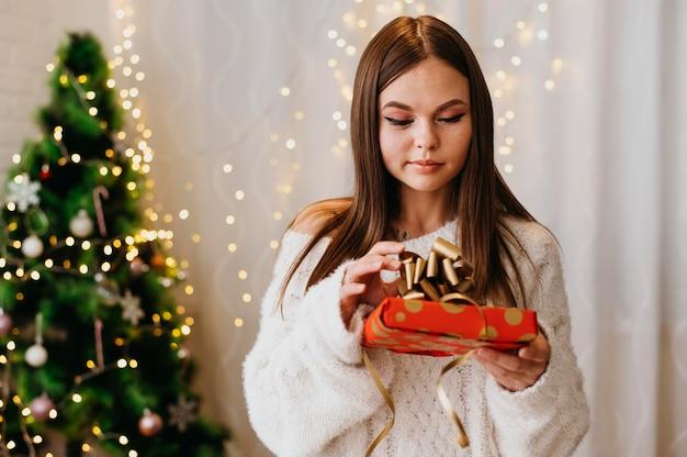 Jovem mulher segurando uma árvore de natal dentro de casa