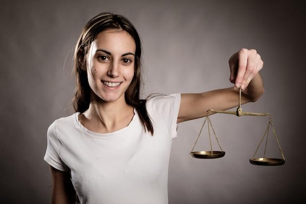 Jovem mulher segurando uma balança da justiça, olhando para a câmera
