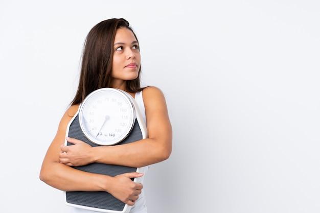 Jovem mulher segurando uma balança sobre parede isolada