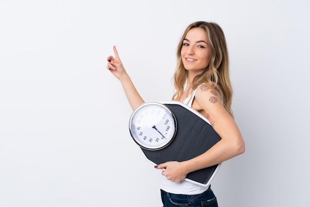 Jovem mulher segurando uma balança sobre parede