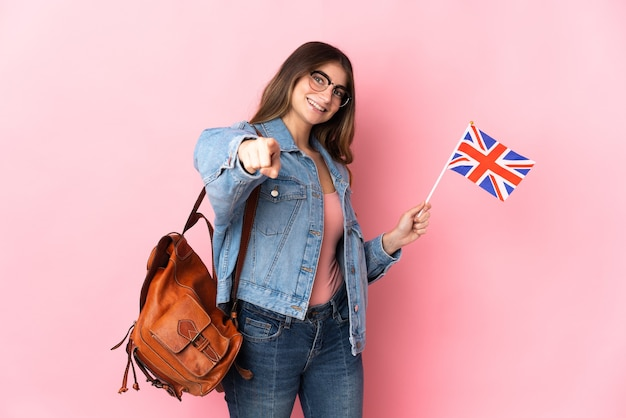 Jovem mulher segurando uma bandeira do reino unido isolada em uma rosa apontando para a frente com uma expressão feliz