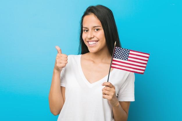 Jovem mulher segurando uma bandeira dos estados unidos, sorrindo e levantando o polegar