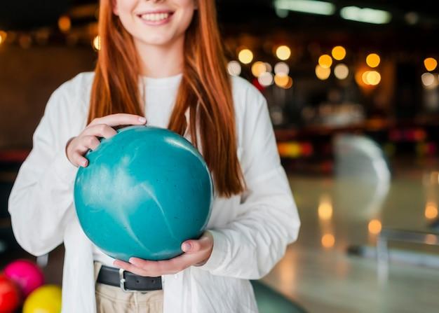 Jovem mulher segurando uma bola de boliche turquesa