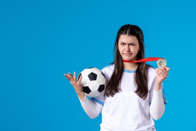Jovem mulher segurando uma bola de futebol de frente