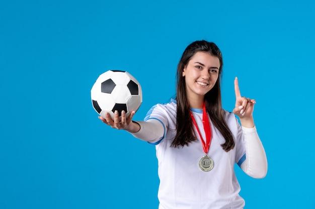 Jovem mulher segurando uma bola de futebol na parede azul de frente