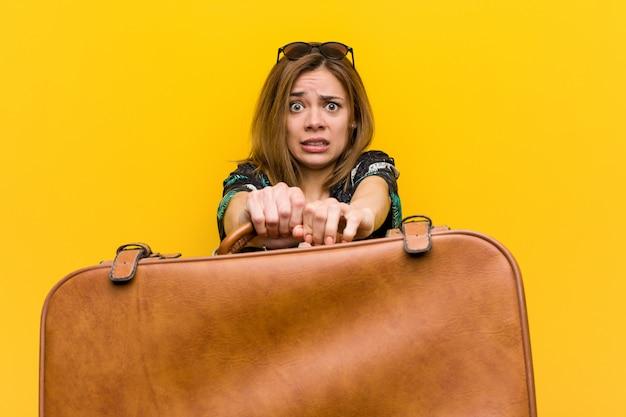Jovem mulher segurando uma bolsa de couro com medo de suas férias, ela tem fobia para voar.