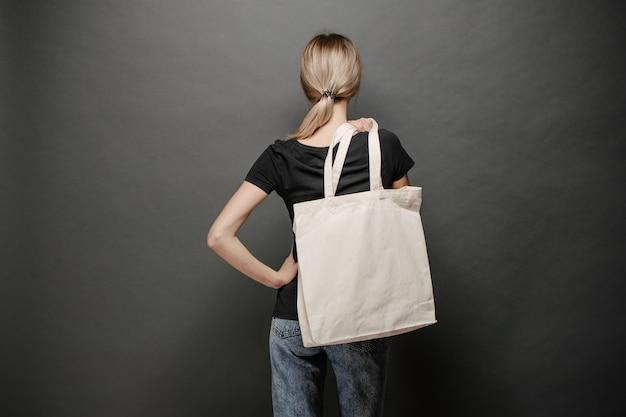 Jovem mulher segurando uma bolsa ecológica têxtil branca contra um fundo cinza. ecologia ou conceito de proteção do meio ambiente. saco ecológico branco para mock up.