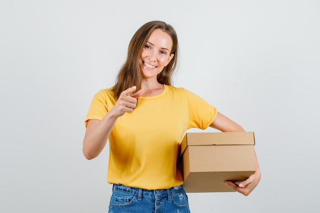 Jovem mulher segurando uma caixa de papelão com o dedo fazendo o sinal em uma camiseta, shorts e parecendo feliz