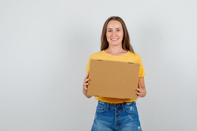 Jovem mulher segurando uma caixa de papelão e sorrindo em camiseta e shorts
