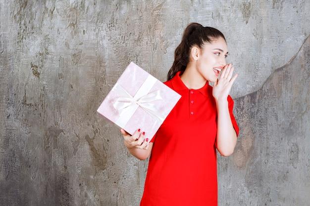 Jovem mulher segurando uma caixa de presente rosa embrulhada com fita branca e gritando em voz alta.