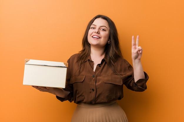 Jovem mulher segurando uma caixa mostrando sinal de vitória e sorrindo amplamente.