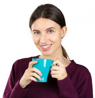 Jovem mulher segurando uma caneca com uma bebida quente, isolada no fundo branco