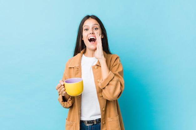 Jovem mulher segurando uma caneca de café gritando animado para a frente