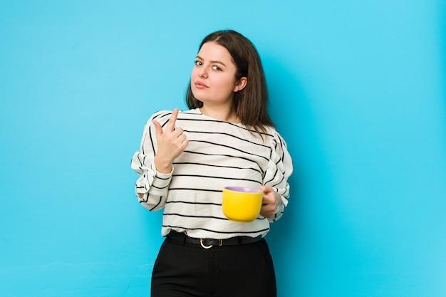 Jovem mulher segurando uma caneca de chá apontando com o dedo para você como se estivesse convidando se aproximar.