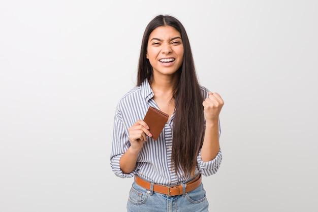 Jovem mulher segurando uma carteira torcendo despreocupada e animada