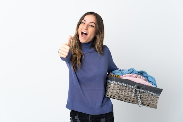 Jovem mulher segurando uma cesta de roupas posando isolada contra a parede em branco