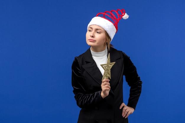Jovem mulher segurando uma decoração em forma de estrela na parede azul, ano novo, natal