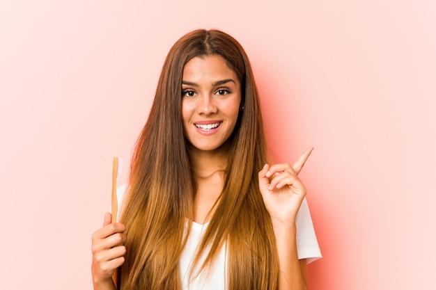 Jovem mulher segurando uma escova de dentes sorrindo alegremente apontando com o dedo indicador fora