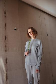 Jovem mulher segurando uma folha de samambaia com um pano de fundo de lona
