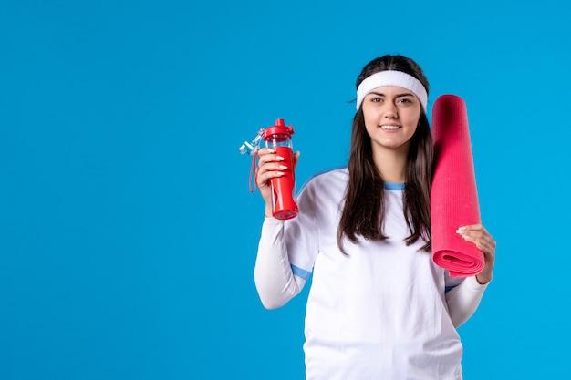 Jovem mulher segurando uma garrafa de água e um tapete para exercícios na parede azul.