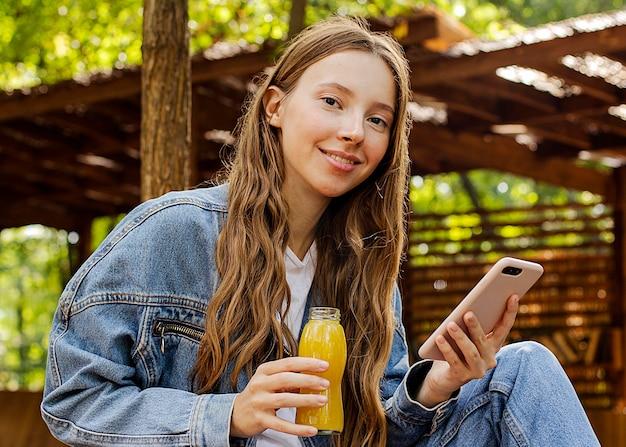 Jovem mulher segurando uma garrafa de suco fresco e um telefone