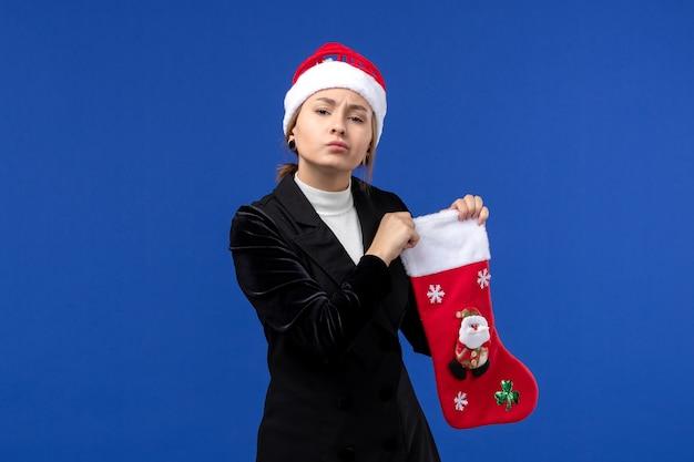 Jovem mulher segurando uma grande meia de natal na parede azul, vista frontal, feriado de véspera de ano novo