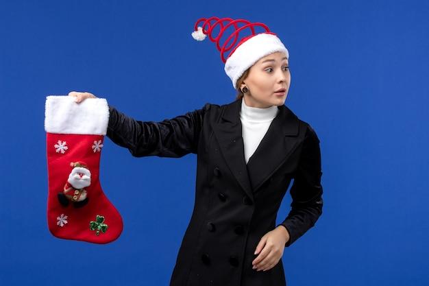 Jovem mulher segurando uma grande meia de natal na parede azul, vista frontal, feriados de véspera de ano novo