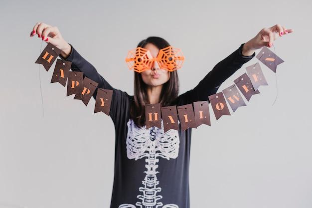 Jovem mulher segurando uma guirlanda com sinal de feliz dia das bruxas. estilo de vida dentro de casa. traje esqueleto