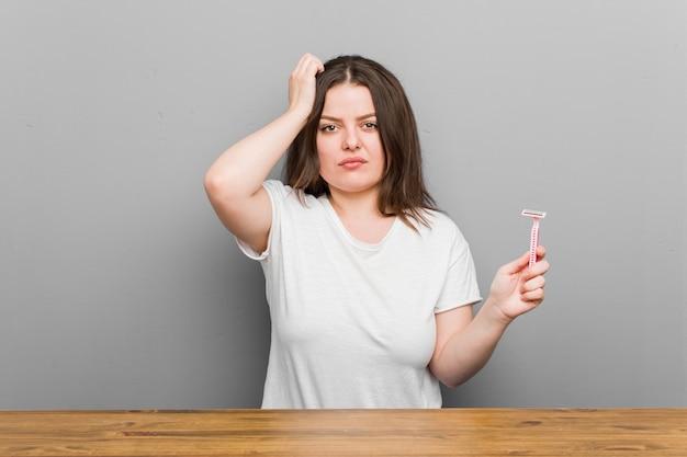 Jovem mulher segurando uma lâmina de barbear estar chocada, ela se lembrou de uma reunião importante.