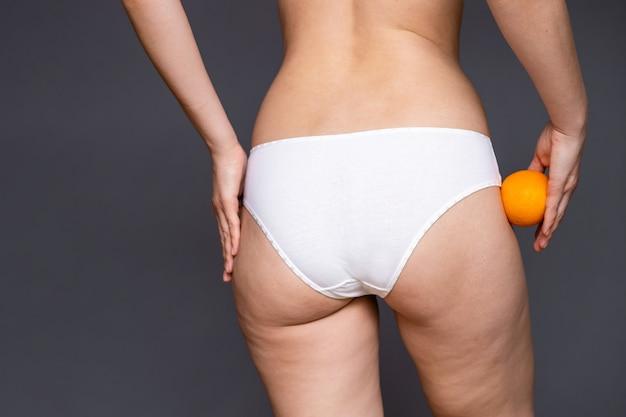 Jovem mulher segurando uma laranja em uma parede de luz. conceito de problema de celulite