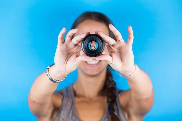 Jovem mulher segurando uma lente fotográfica e olhando através dela