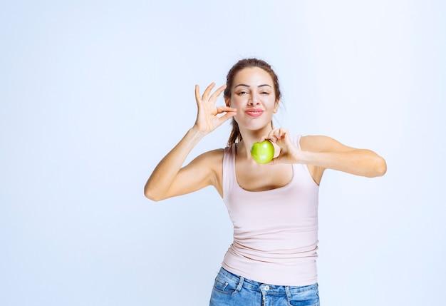 Jovem mulher segurando uma maçã verde e apreciando o sabor