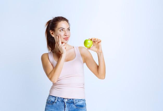 Jovem mulher segurando uma maçã verde e pensando