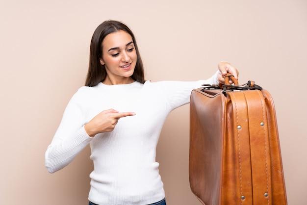 Jovem mulher segurando uma mala vintage
