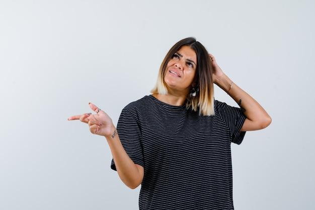 Jovem mulher segurando uma mão na cabeça, apontando para a esquerda com o dedo indicador em um vestido preto e olhando pensativa, vista frontal.