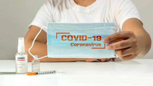 Jovem mulher segurando uma máscara com mensagem covid19 coronavirus em uma máscara